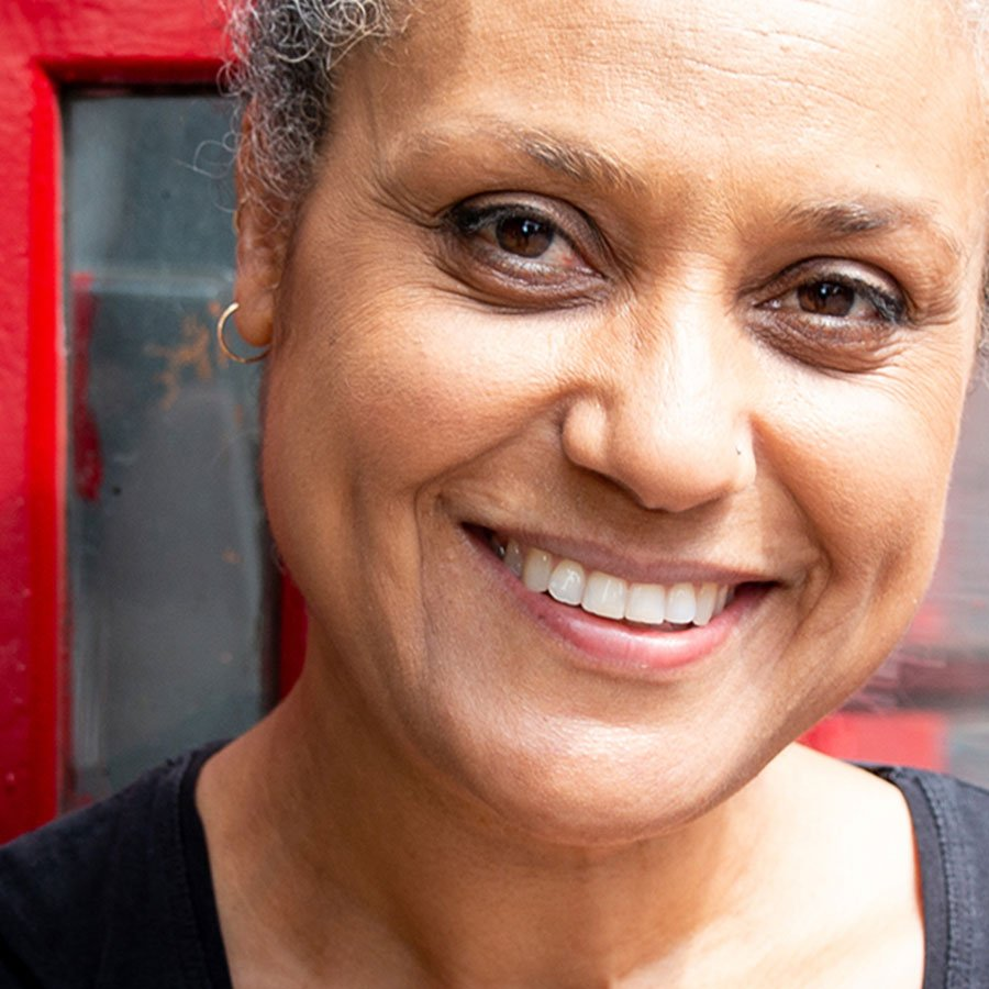 Female smiling with red telephone box in background