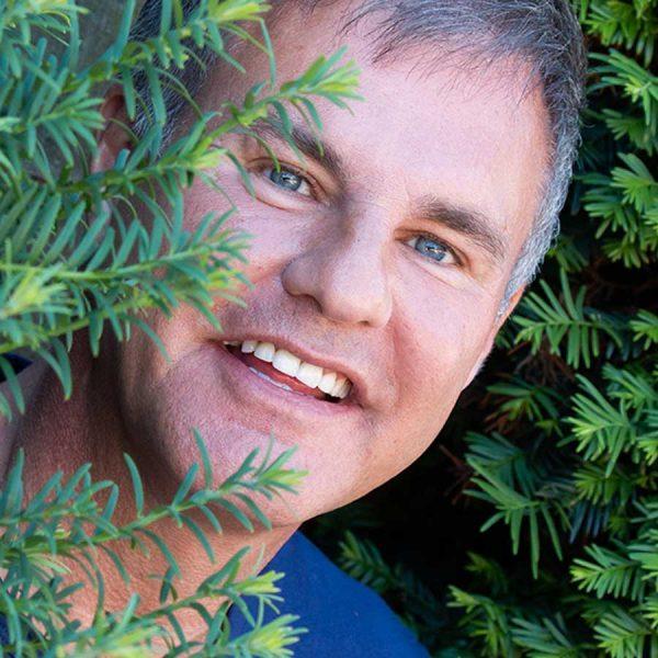 Man peering through bushes