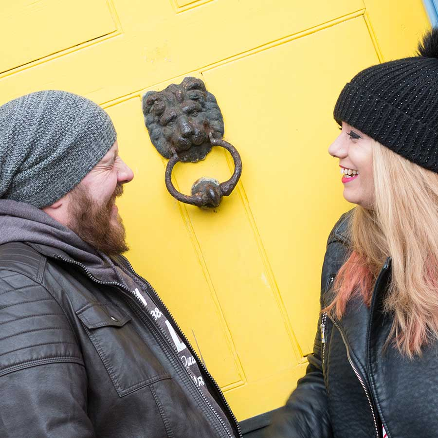 Couple laughing with each other in front of bright yellow door