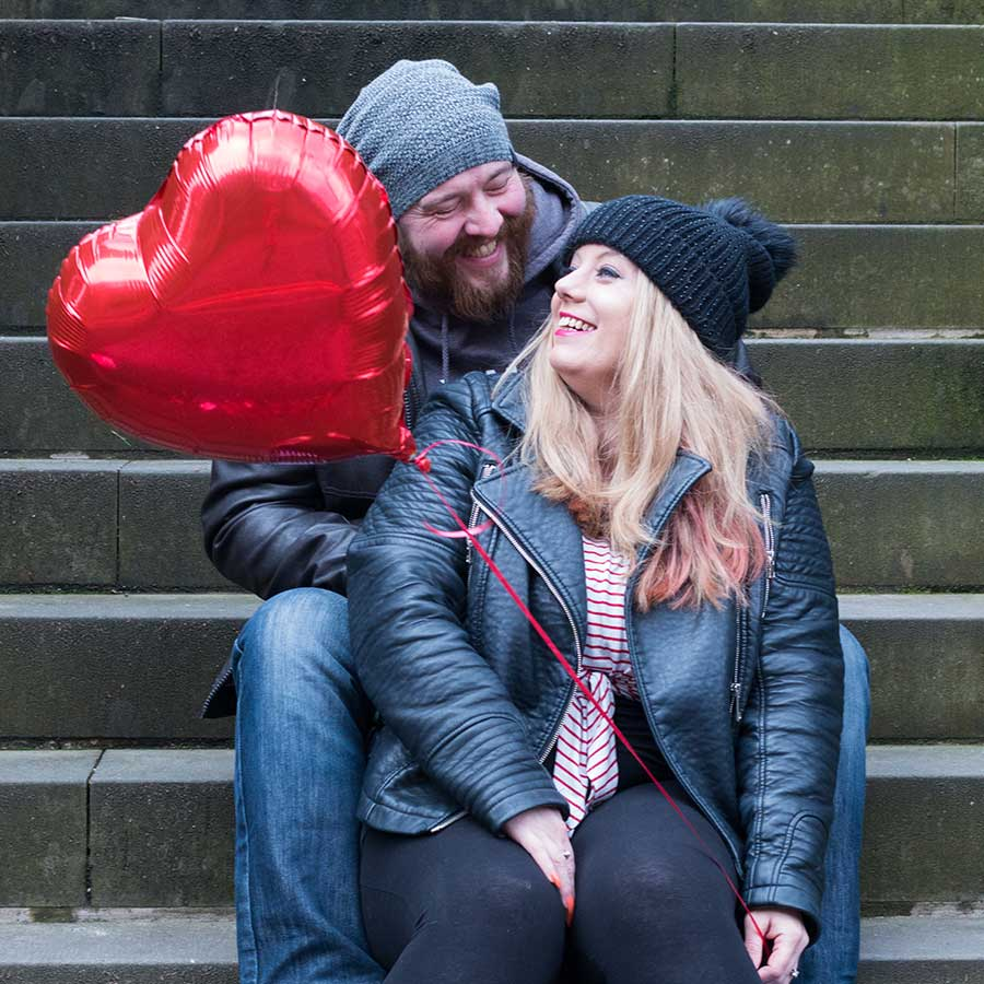A portrait of a couple sat on steps with a red heart balloon on Valentines Day.
