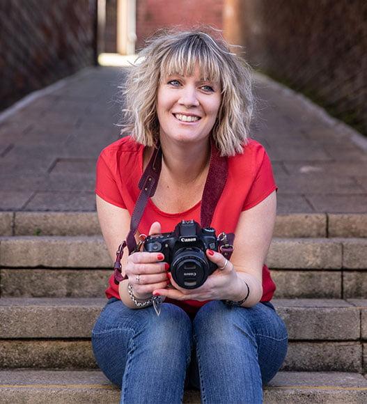 Gemma Wilks sat on steps with her camera in Hockley, Nottingham