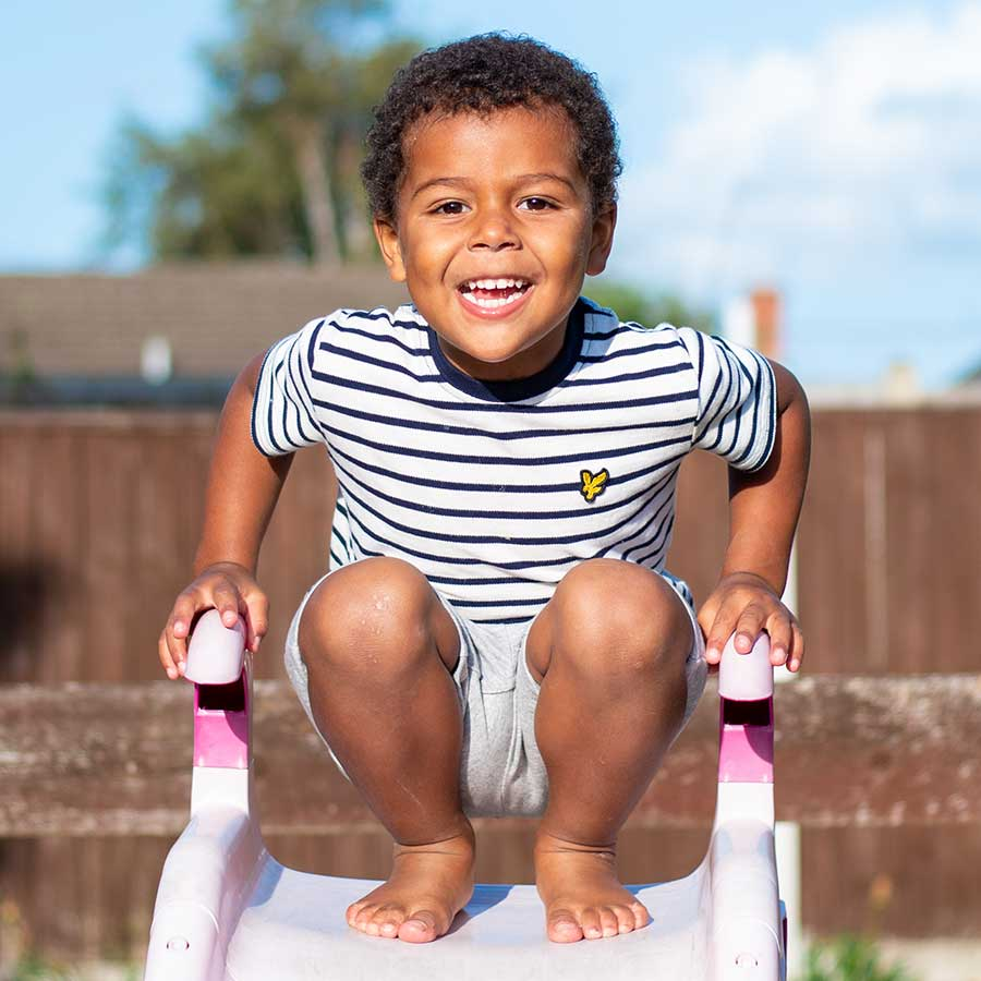 Children's portrait of a young boy on a slide