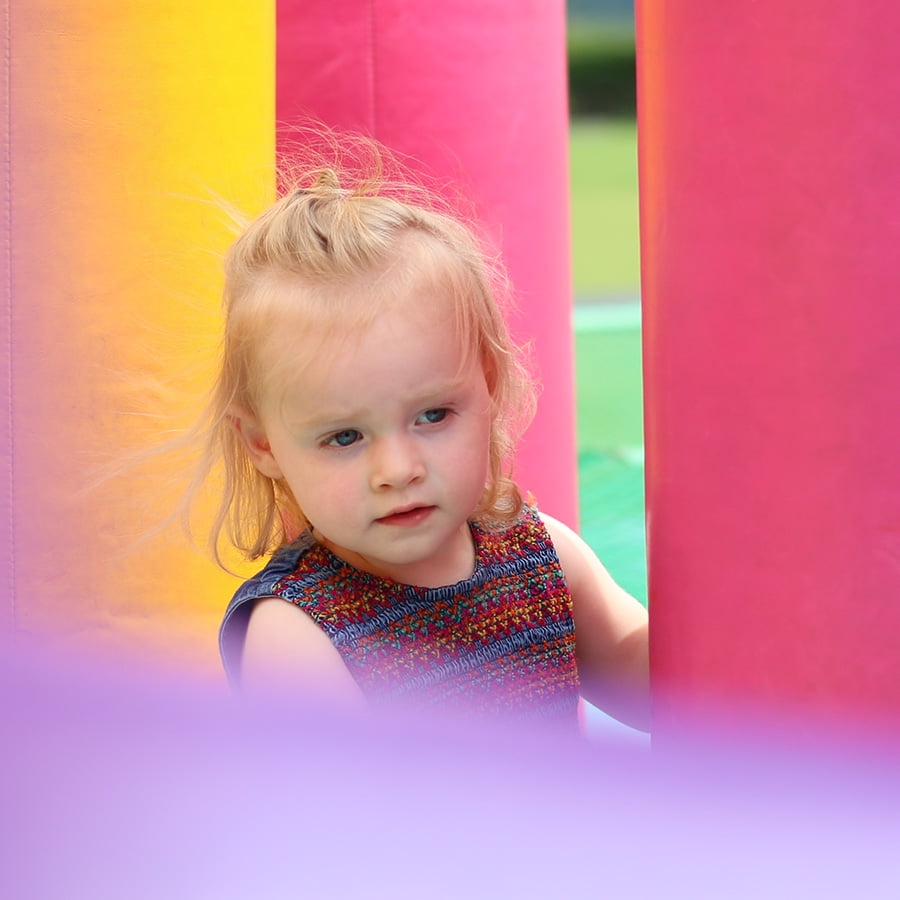 Children's portrait of a young girl having fun on inflatables