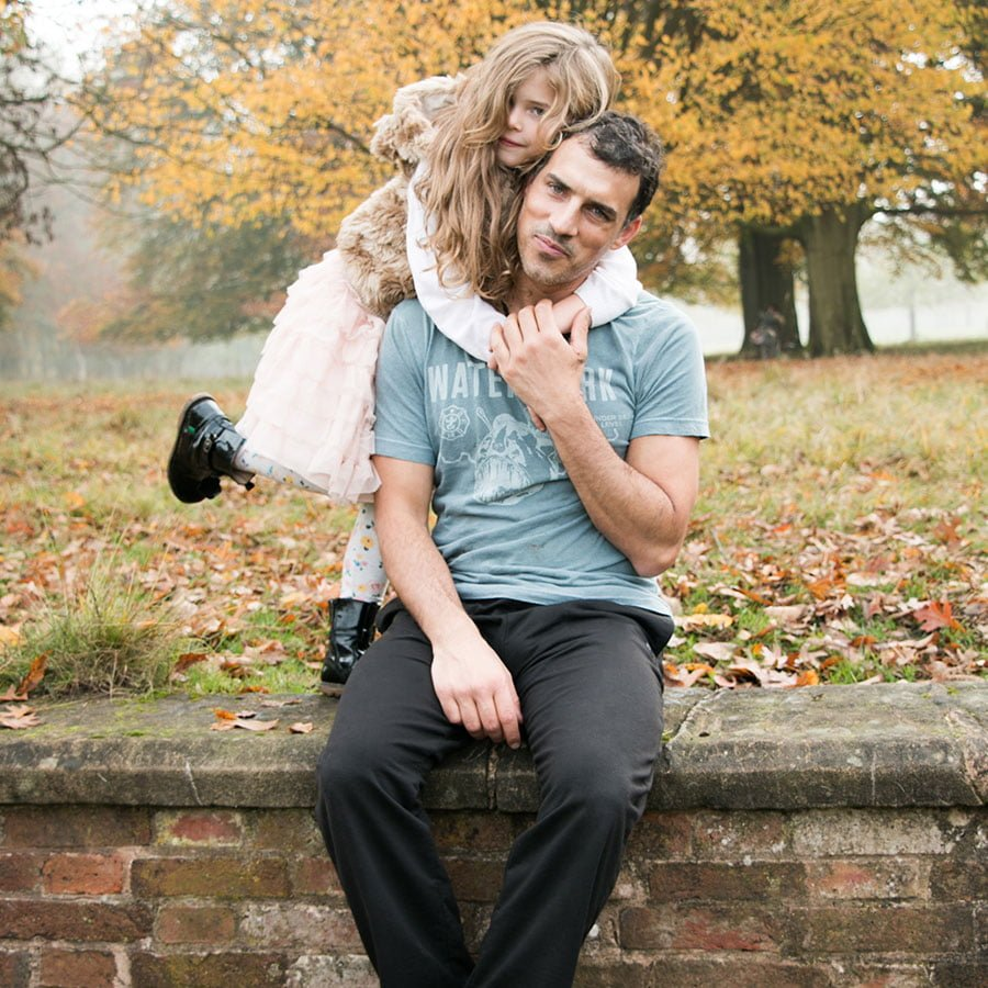 Father and daughter posing together on an autumnal day