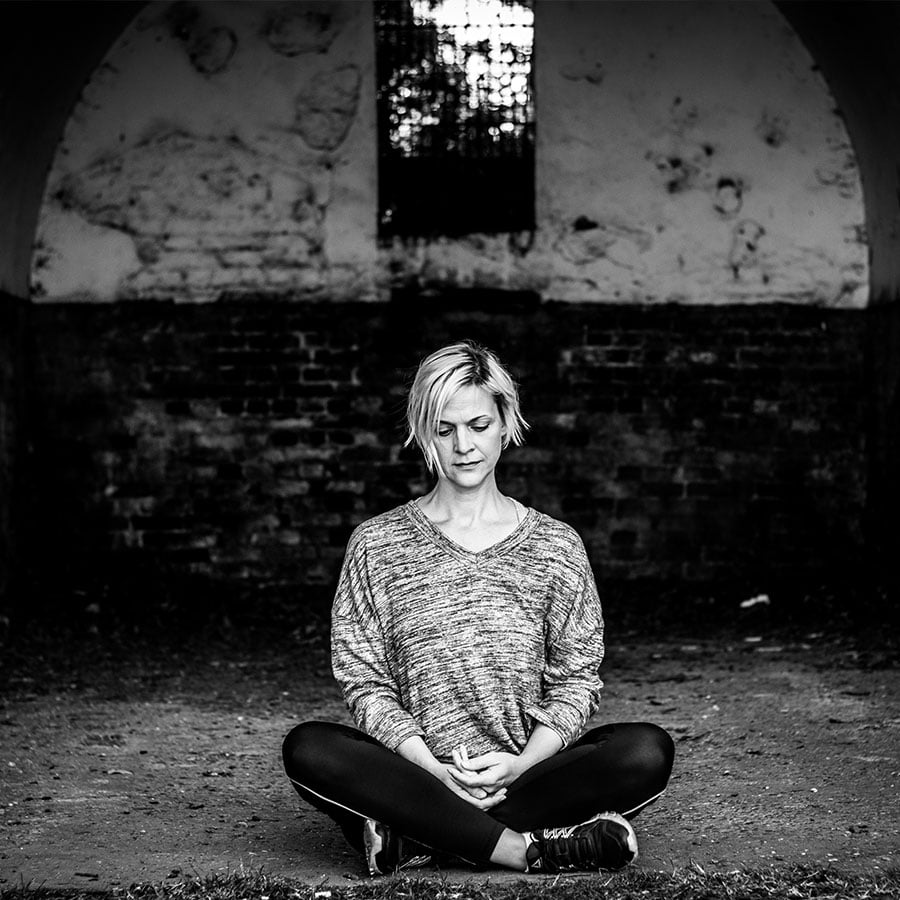A woman meditating during her brand photography shoot at Wollaton Park